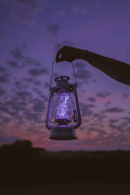 Crop faceless person with luminous lantern in hand against dark night sky in nature