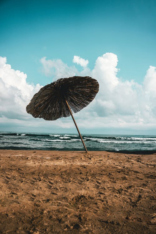 Lonely parasol on beach near sea