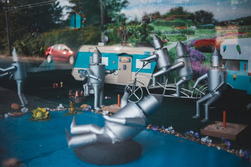 Creative composition in store window of funny steel figurines simulating people activities on street
