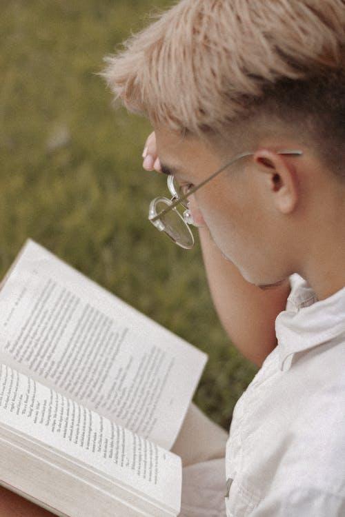 Pemuda Berkacamata Membaca Buku Di Taman