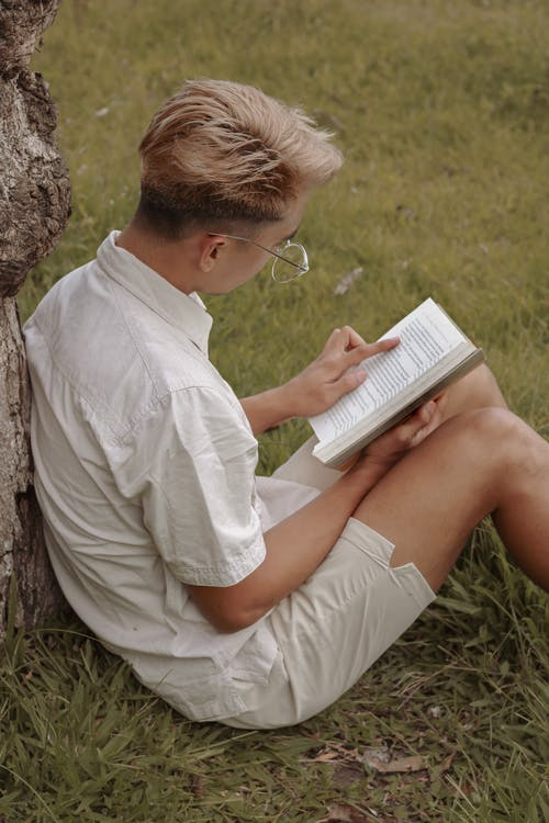 Teenager leaning on tree and reading book