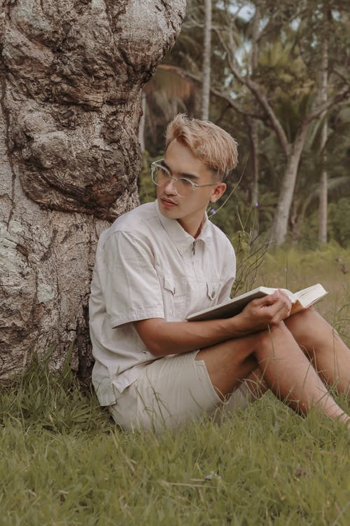 Calm young man sitting near tree with book