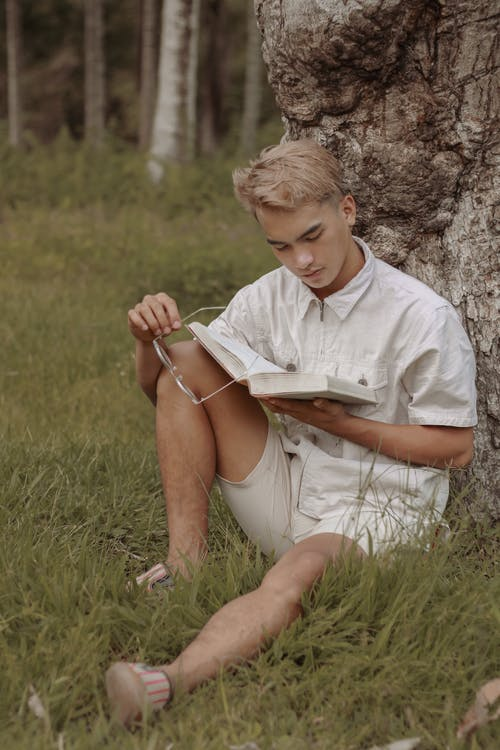 Concentrated man reading book on grassy lawn near tree