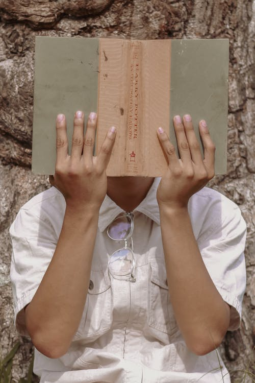 Faceless person hiding face behind opened book