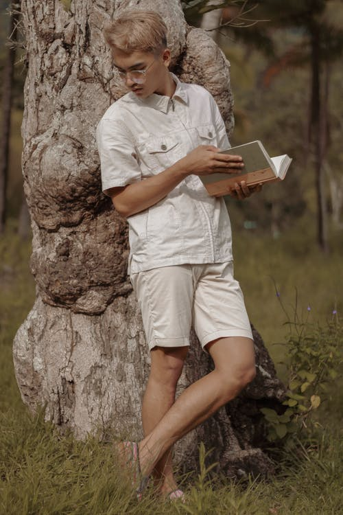 Thoughtful young guy reading book in nature
