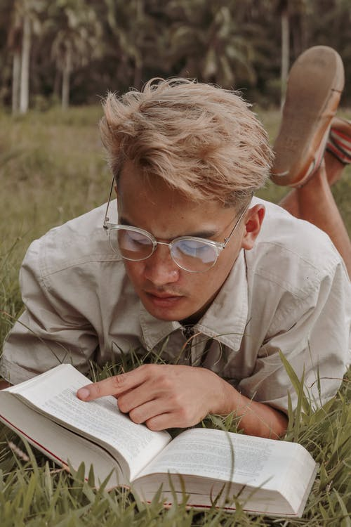 Focused young male student in eyeglasses and stylish outfit lying on grass in park and reading textbook during summer vacation