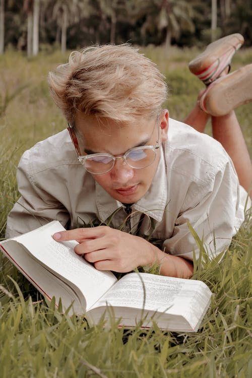 Focused male teenager reading novel in green park