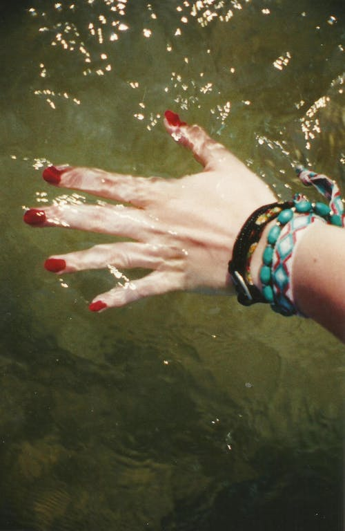 Hand of a Person With Red Nail Polish Touching The Water