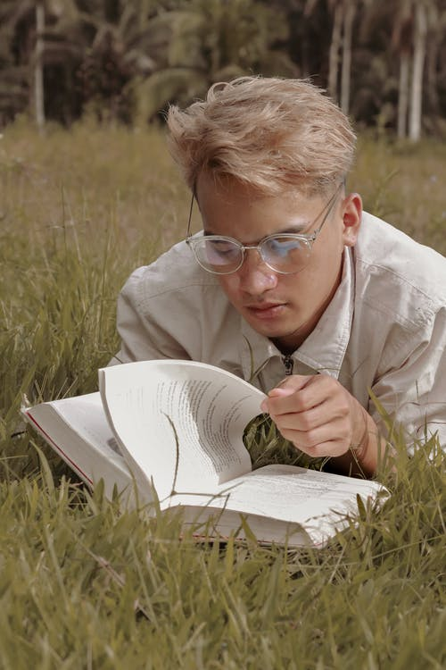 Concentrated young guy with blond hair in casual clothes and eyeglasses searching information in book while lying on grass in park