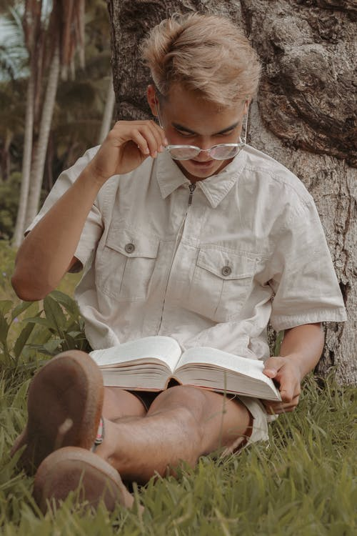 Positive young man reading book leaning on tree in park