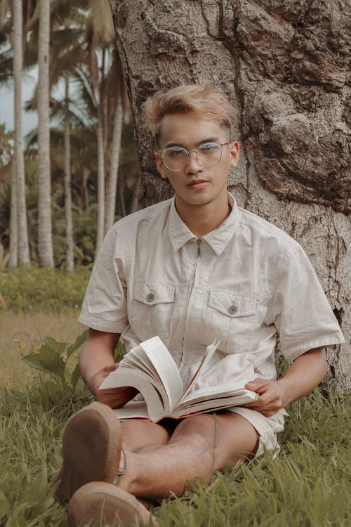Stylish young ethnic guy relaxing on grassy ground with interesting book