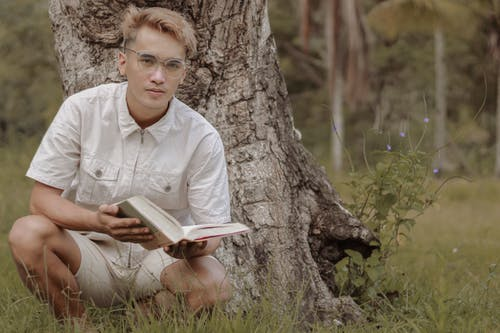 Handsome young ethnic man reading novel near tree in daytime