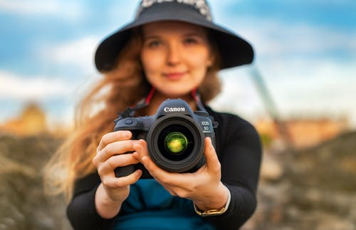 Woman in Blue Shirt Holding Black Nikon Dslr Camera