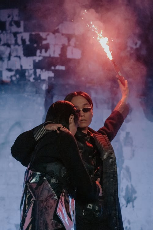 Woman in Black and Red Jacket Holding Red Smoke