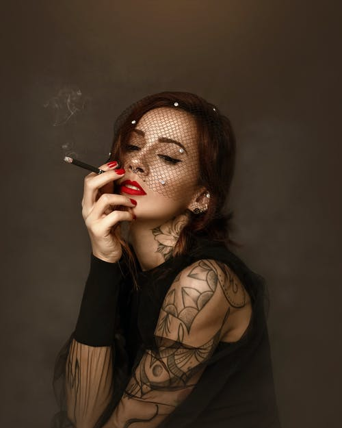 Young female with bright makeup in stylish veil and black clothes smoking cigarette in studio