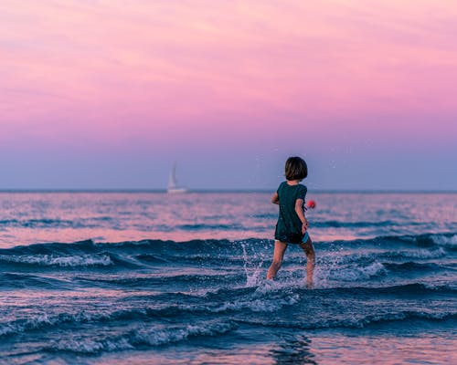 Unrecognizable child running in sea at sunset