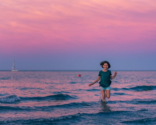 Cheerful girl running alone in sea