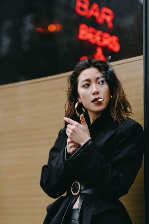Stylish Asian woman smoking cigarette on city street