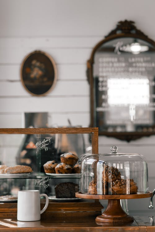 Assorted tasty muffins and puffs on stand near piece of chocolate cake in modern pastry shop