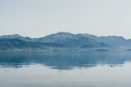Picturesque view of spacious tranquil lake surrounded by hilly coast on foggy morning