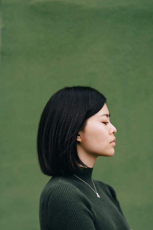 Zelfverzekerde Aziatische Vrouw Tegen Een Groene Achtergrond