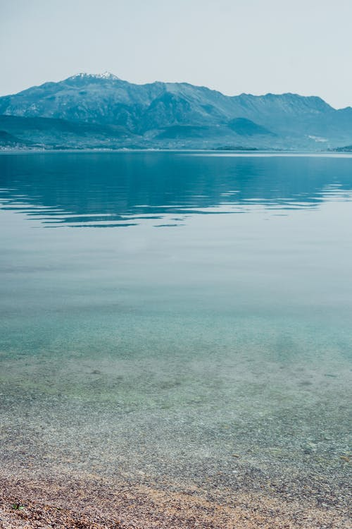 Picturesque view of rippling lake water and sandy shore with small stones near rocky hills