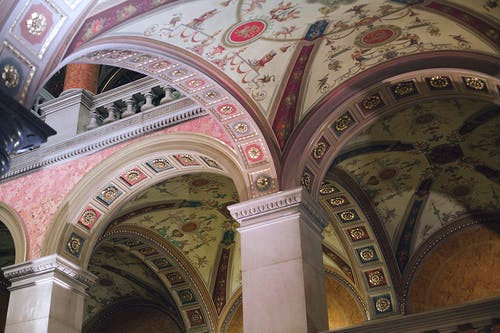 From below of aged stone columns under ornamental ceiling of classic palace in city