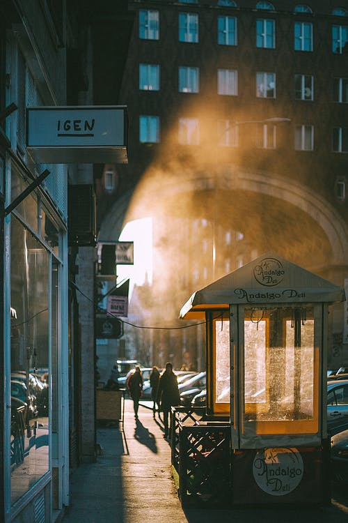 Unrecognizable people walking along arched passage at sunrise