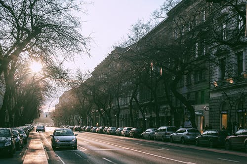 Wide straight road with parked cars in cityscape on sunny morning