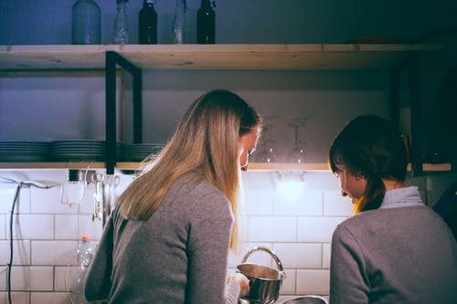 Cheerful women cooking together in kitchen