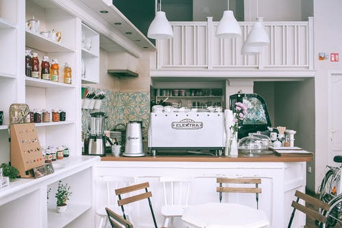 White kitchen set with coffee maker and appliances in small cozy coffee shop with flowers and table in daylight