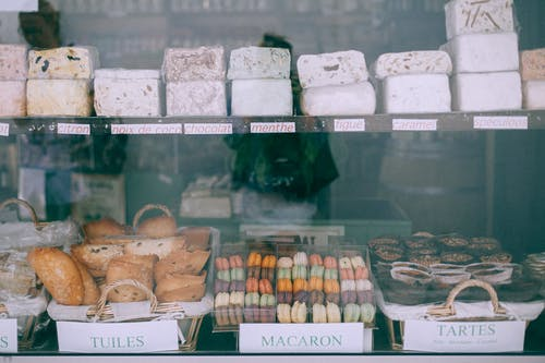 Assorted yummy sweets and bakery products places on counter of confectionery shop in daytime