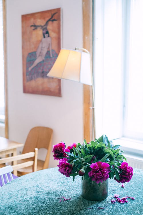 Vase with flowers on table in room