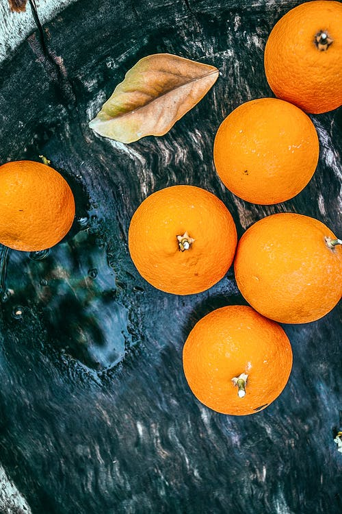 Top view of fresh orange tangerines and dry leaf on dark shabby tray