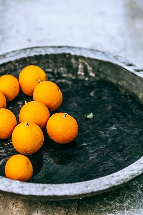 High angle of ripe appetizing tangerines on metal tray on table at home