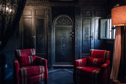 Interior of old fashioned room with ornamental wooden wardrobe and cozy furniture in apartment