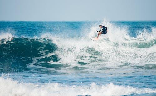 Full body powerful male surfer in swimwear surfing surfboard on strong foamy sea waves under clear blue sky