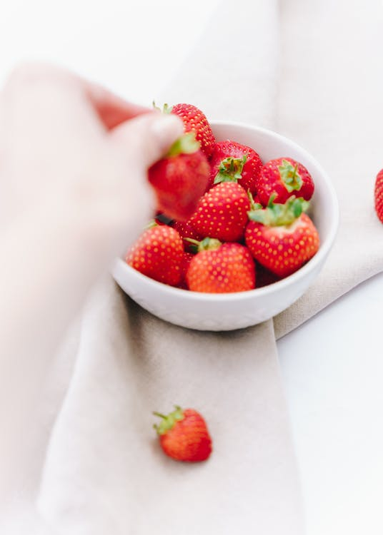 From above of crop person taking fresh strawberry from bowl on fabric on table
