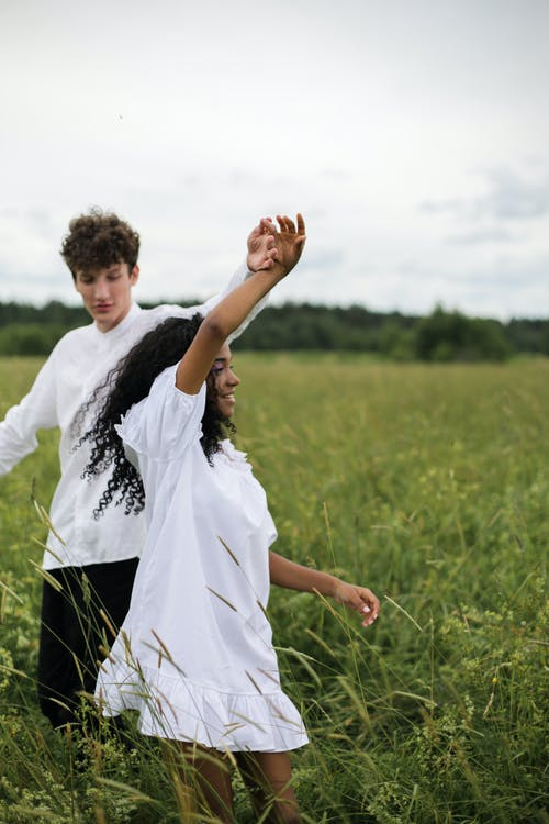 Man in White Shirt Holding Woman in White Dress on Green Grass Field
