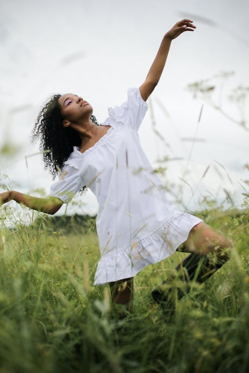 Woman in White Dress Shirt and Yellow Skirt Standing on Green Grass Field