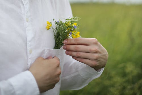 Person Holding Yellow and White Flower Bouquet