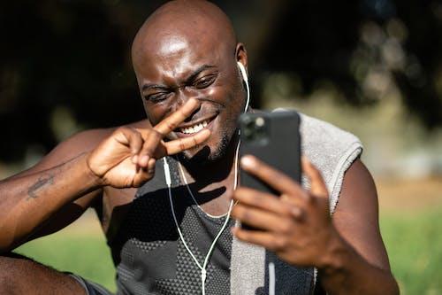 Man in Gray Crew Neck Shirt Holding Black Smartphone