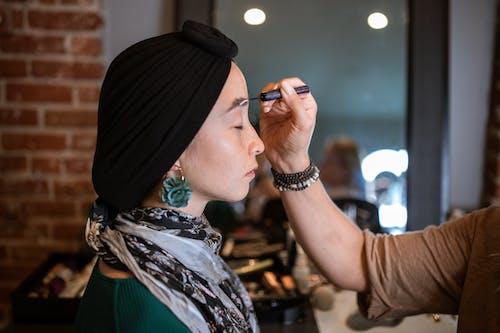 женщина в зелено белом платье с цветочным принтом в черном хиджабе