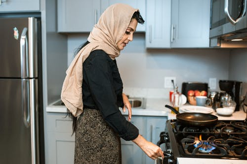Ethnic woman in headscarf switching on stove