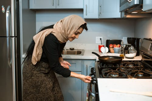 Cheerful ethnic woman switching stove before cooking