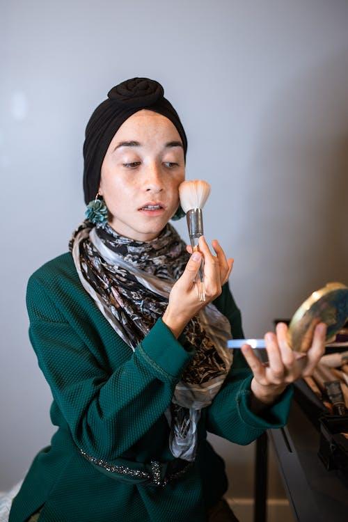 Femme En Hijab Noir Tenant Un Pinceau De Maquillage
