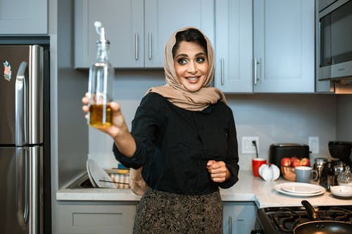 Cheerful ethnic woman showing bottle with oil