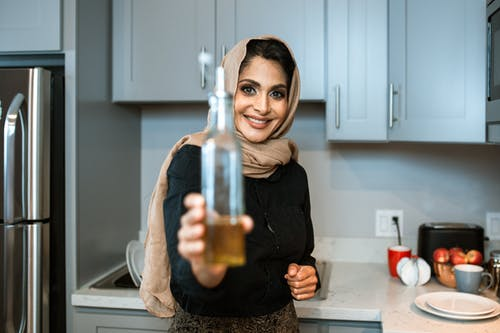 Happy ethnic female in headscarf showing bottle of organic olive oil and looking at camera with smile while cooking in contemporary kitchen