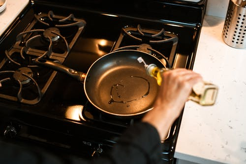 Crop unrecognizable chef pouring oil in frying pan