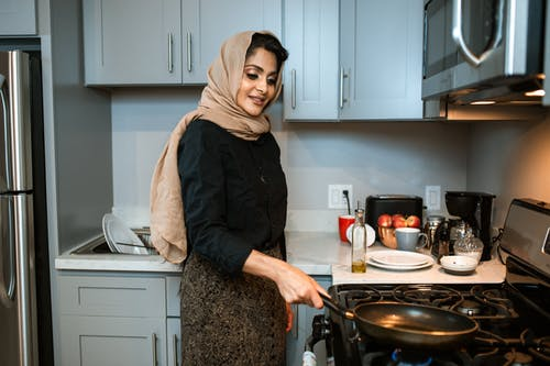 Content Arabic woman with frying pan in modern kitchen